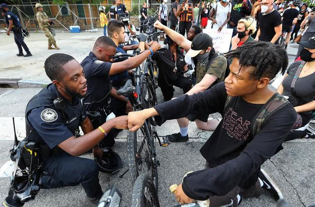 police kneeling at protest